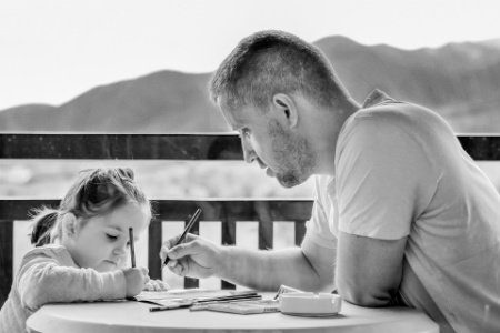 Photo of Father & Daughter Writing on Paper