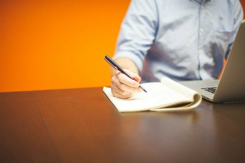 Photo of Man Writing in a Notebook