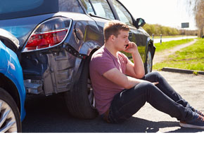 Photo of Man Sitting By Broke Down Car